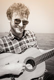 Young man hipster playing guitar by sea ocean. Stock Images