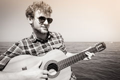 Young man hipster playing guitar by sea ocean. Stock Image