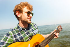 Young man hipster playing guitar by sea ocean. Stock Photos
