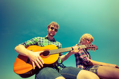 Young man hipster playing guitar for woman. Royalty Free Stock Photos