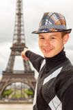 Young man hipster shows the Eiffel tower, Paris, France. Young man hipster in a hat and vest shows the Eiffel tower (La Tour Eiffel) in Paris, France Royalty Free Stock Photos