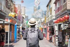 Young man hipster traveling with backpack and hat, happy Solo traveler walking at Chinatown street market in Singapore. landmark. And popular for tourist stock image