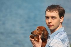 Young man and his adorable dachshund against water Stock Photo