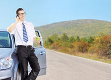 Young man on his automobile drinking coffee and talking on a pho Stock Images