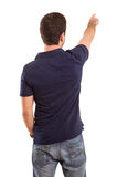 Young man. A young man with his back turned to camera, pointing to something Stock Photo