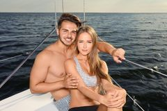 Young man and his beautiful girlfriend in bikini sitting. Young men and his beautiful girlfriend in bikini sitting on yacht. Happy couple on vacation stock images