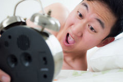 Young man on his bedside, knowing that he overslept and late for Stock Images