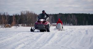Young man with his brother on snowmobile stock footage