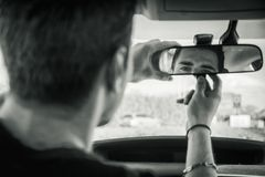Young man in his car adjusting rear view mirror. Young handsome man in his car adjusting rear view mirror during day Stock Image