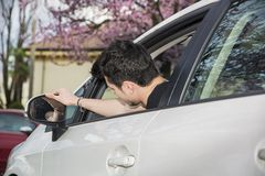 Young man in his car adjusting rear view mirror Royalty Free Stock Images