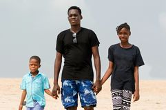 A young man and his children at the beach stock image
