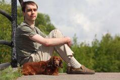 Young man and his dachshund sits outdoor Stock Photo
