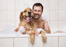 Young man and his dog in bubble bath Stock Image