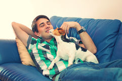 Young man and his dog on a couch. Portrait of an attractive young man playing with his cute dog lying on couch in his living room over white background Royalty Free Stock Photos