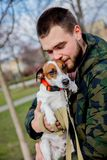 Young man with his dog, Jack Russell Terrier,. On the city street in spring time stock photography