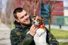 Young man with his dog, Jack Russell Terrier,. On the city street in spring time royalty free stock photography