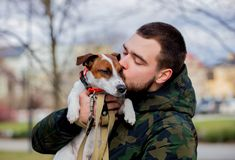 Young man with his dog, Jack Russell Terrier,. On the city street in spring time royalty free stock photos