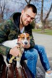 Young man with his dog, Jack Russell Terrier,. On the city street in spring time royalty free stock images