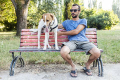 Young man with his dog sitting on bench Royalty Free Stock Images