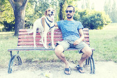 Young man with his dog sitting on bench Royalty Free Stock Photo