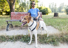 Young man with his dog sitting on bench Stock Image