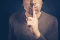 Young man with his finger on his lips Royalty Free Stock Photo