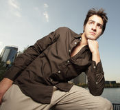 Young man with his fist under his chin. Young man glancing away with his fist under his chin Royalty Free Stock Photo