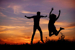 A young man with his girlfriend jump on background sunset silhouette Stock Image