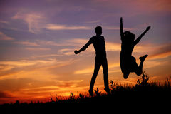 A young man with his girlfriend jump on background sunset silhouette Royalty Free Stock Photo