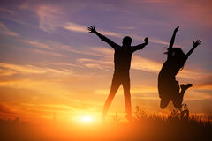 A young man with his girlfriend jump on background sunset silhouette Royalty Free Stock Photography