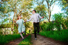 A young man with his girlfriend jump on the road in the sunny village royalty free stock photo