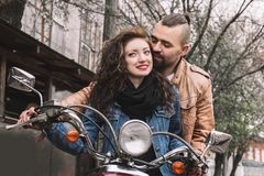 Young man and his girlfriend riding a motorcycle. royalty free stock image