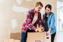 Young man and his girlfriend sealing a box while renovating thei Stock Images