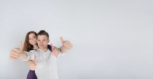 Young man with his girlfriend showing thumbs up Royalty Free Stock Images