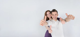 Young man with his girlfriend showing thumbs up Stock Photo