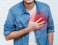 Young man with his hand holding his chest. Young man having heart attack Royalty Free Stock Image