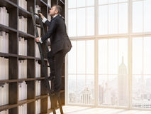 Young man in his home library. Young man in suit is climbing up ladder in house library. New York city seen through window. Concept of information searching. 3d Stock Photos