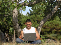 Young man with his laptop. Young man working outside under the tree royalty free stock photo