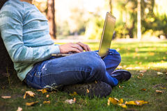 Young man with his laptop in city park outdoor. Man in blue jumper and black sneakers Royalty Free Stock Image