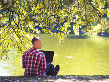 Young man with his laptop in city park outdoor. Man in red short smiling Royalty Free Stock Photo