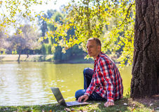 Young man with his laptop in city park outdoor. Man in red short smiling Royalty Free Stock Image