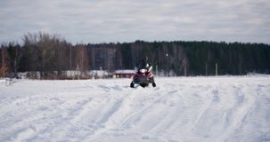 Young man with his little brother on snowmobile stock video