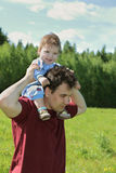 Young man with his little cute son on shoulders Stock Photography