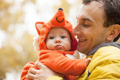 Young man and his little son in fox costume. Young Caucasian men and his little son in fox costume in autumn park Stock Photos