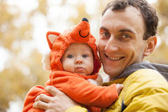 Young man and his little son in fox costume. Young Caucasian men and his little son in fox costume in autumn park Royalty Free Stock Images