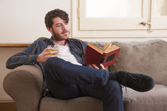 Young man. At his living room with a plaid shirt and a book Royalty Free Stock Image