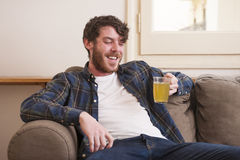 Young man. At his living room with a plaid shirt and a book Stock Photos