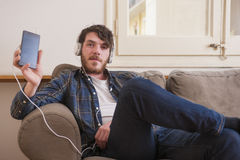 Young man. At his living room with a plaid shirt listening to music Stock Photos