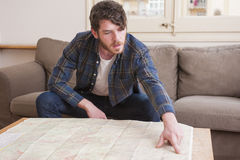 Young man. At his living room with a plaid shirt and a map Stock Image