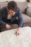 Young man. At his living room with a plaid shirt and a map Stock Photos